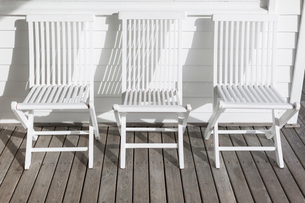White folding chairs in a row on sunny patioの写真素材 [FYI02177568]