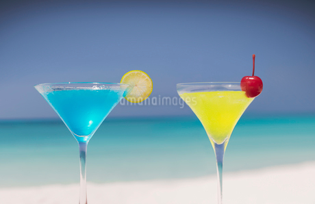 Blue and yellow cocktails in martini glasses on tropical beachの写真素材 [FYI02177576]