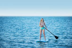 Young woman in bikini paddleboarding on summer oceanの写真素材 [FYI02177583]