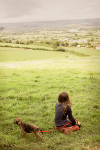 Girl with puppy dog in rural, green countryside fieldの写真素材 [FYI02177584]