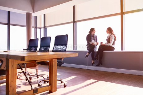 Businesswomen talking and drinking coffee at sunny conference room windowの写真素材 [FYI02177593]
