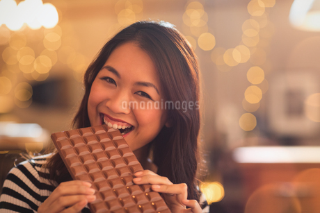 Portrait Chinese woman with sweet tooth craving biting into large chocolate barの写真素材 [FYI02177594]