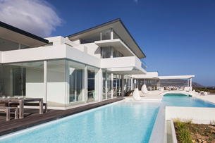 Sunny, tranquil modern luxury home showcase exterior with swimming poolの写真素材 [FYI02177598]