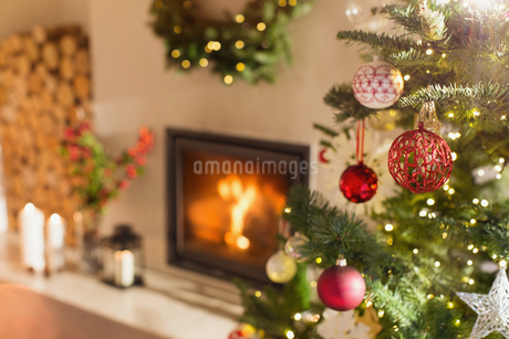 Red and white ornaments hanging from Christmas tree next to fireplaceの写真素材 [FYI02177604]