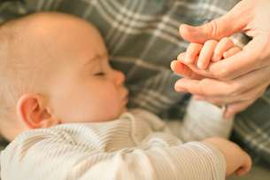 Close up sleeping baby boy holding hands with fatherの写真素材 [FYI02177616]