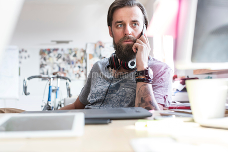 Pensive design professional with headphones talking on cell phone at deskの写真素材 [FYI02177617]