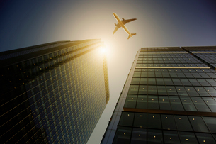 Airplane flying over highrise buildings, travel conceptの写真素材 [FYI02177643]