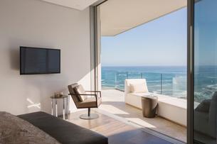 Bedroom open to sunny luxury home showcase balcony with ocean viewの写真素材 [FYI02177692]