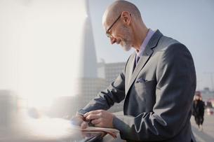 Businessman checking smart watch on sunny urban sidewalk, London, UKの写真素材 [FYI02177713]