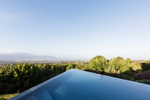 Modern, geometric infinity pool with sunny view under blue skyの写真素材 [FYI02177765]