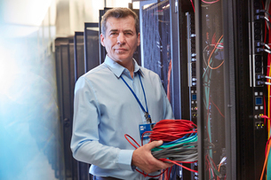 Portrait serious male IT technician holding cables in server roomの写真素材 [FYI02177769]