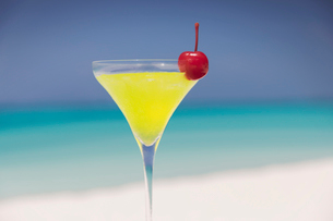 Close up yellow cocktail with cherry in martini glass on sunny tropical beachの写真素材 [FYI02177774]