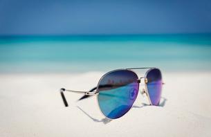 Close up aviator sunglasses in sand on sunny tropical ocean beachの写真素材 [FYI02177778]