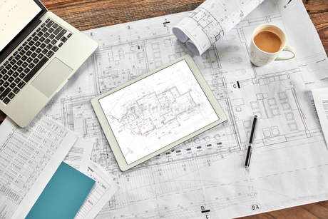 Still life digital and complex paper blueprints with coffee and laptopの写真素材 [FYI02177783]