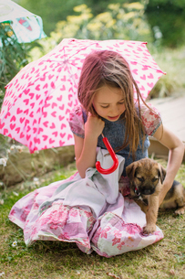 Girl with puppy dog holding heart-shape umbrella in grassの写真素材 [FYI02177811]