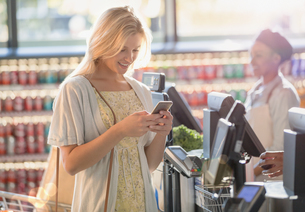 Smiling young woman texting with cell phone at grocery store market checkoutの写真素材 [FYI02177840]