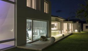 Illuminated modern luxury home showcase exterior patio at nightの写真素材 [FYI02177852]