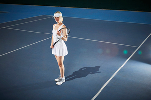 Young female tennis player holding tennis racket on sunny blue tennis courtの写真素材 [FYI02177864]