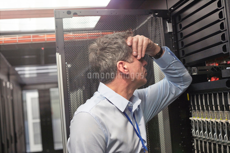 Frustrated IT technician at panel in server roomの写真素材 [FYI02177870]