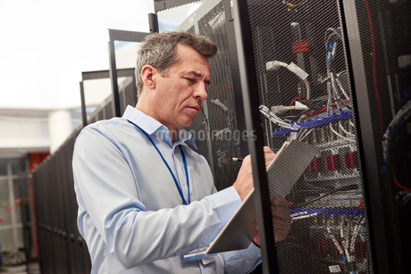 Male IT technician writing on clipboard at panel in server roomの写真素材 [FYI02177890]