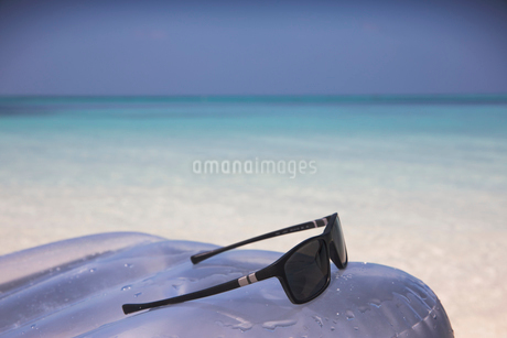 Sunglasses on inflatable raft in tropical blue oceanの写真素材 [FYI02177935]