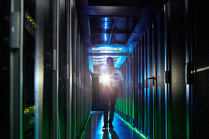 Male security guard with flashlight walking in dark server roomの写真素材 [FYI02177947]