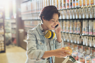 Smiling young woman with headphones talking on cell phone grocery shopping in marketの写真素材 [FYI02177962]