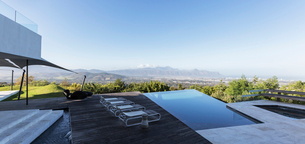 Modern luxury home showcase exterior with infinity pool and mountain view under blue skyの写真素材 [FYI02177994]