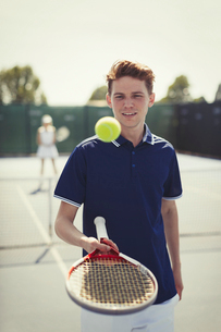 Young male tennis player bouncing tennis ball on tennis racket on tennis courtの写真素材 [FYI02177996]