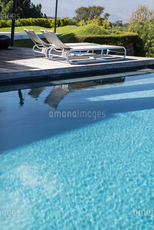 Sunny, tranquil blue swimming pool and lounge chairsの写真素材 [FYI02178024]