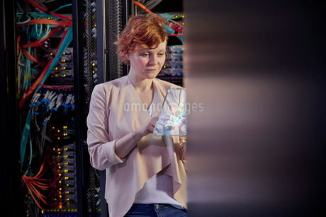 Female IT technician using futuristic digital tablet in server roomの写真素材 [FYI02178031]