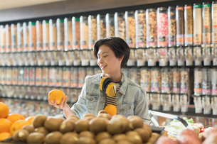 Young woman with headphones grocery shopping, holding orange in marketの写真素材 [FYI02178042]