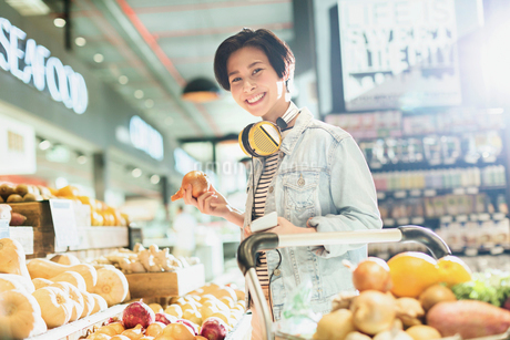 Portrait smiling young woman with headphones grocery shopping in marketの写真素材 [FYI02178055]