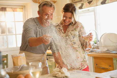 Playful mature couple baking, throwing flour and drinking wine in kitchenの写真素材 [FYI02178069]