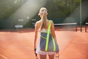 Young female tennis player walking with bag on sunny clay tennis courtの写真素材 [FYI02178086]