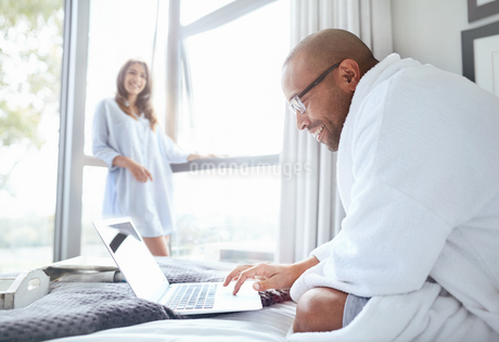 Smiling woman watching boyfriend in bathrobe reading laptop on bedの写真素材 [FYI02178105]