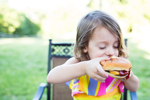 Preschool girl eating messy cheeseburger on patioの写真素材 [FYI02178117]