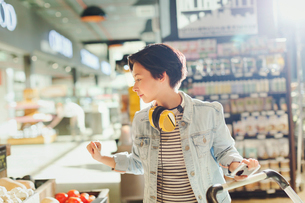Young woman with headphones browsing, grocery shopping in marketの写真素材 [FYI02178127]