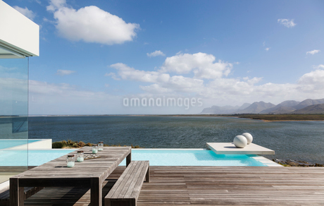 Sunny tranquil modern luxury patio with infinity pool and ocean viewの写真素材 [FYI02178146]