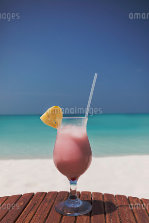 Pink cocktail with pineapple slice and straw on sunny tropical ocean beachの写真素材 [FYI02178148]