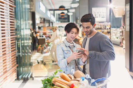 Young couple using cell phone in grocery store marketの写真素材 [FYI02178172]