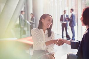Smiling businesswomen handshaking in office lobbyの写真素材 [FYI02178196]