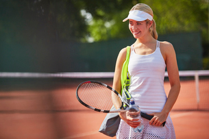 Young female tennis player holding tennis racket and water bottle on sunny tennis courtの写真素材 [FYI02178208]