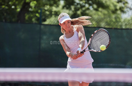 Determined young female tennis player playing tennis, hitting the ball on sunny tennis courtの写真素材 [FYI02178234]