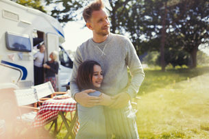 Affectionate father and daughter hugging outside sunny motor homeの写真素材 [FYI02178246]