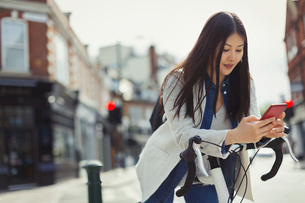 Young woman commuting on bicycle, texting with cell phone on sunny urban streetの写真素材 [FYI02178249]