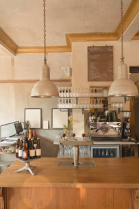 Espresso machine, glasses and bottles behind vintage cafe counterの写真素材 [FYI02178257]