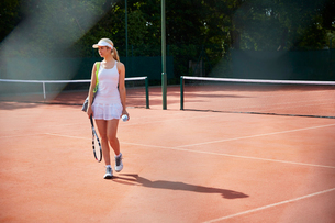 Young female tennis player walking with tennis racket on sunny clay courtの写真素材 [FYI02178269]