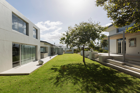 Sunny modern luxury home showcase exterior with grass courtyardの写真素材 [FYI02178274]