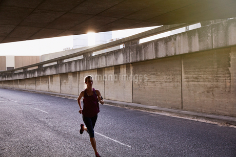Female runner running into urban tunnelの写真素材 [FYI02178286]